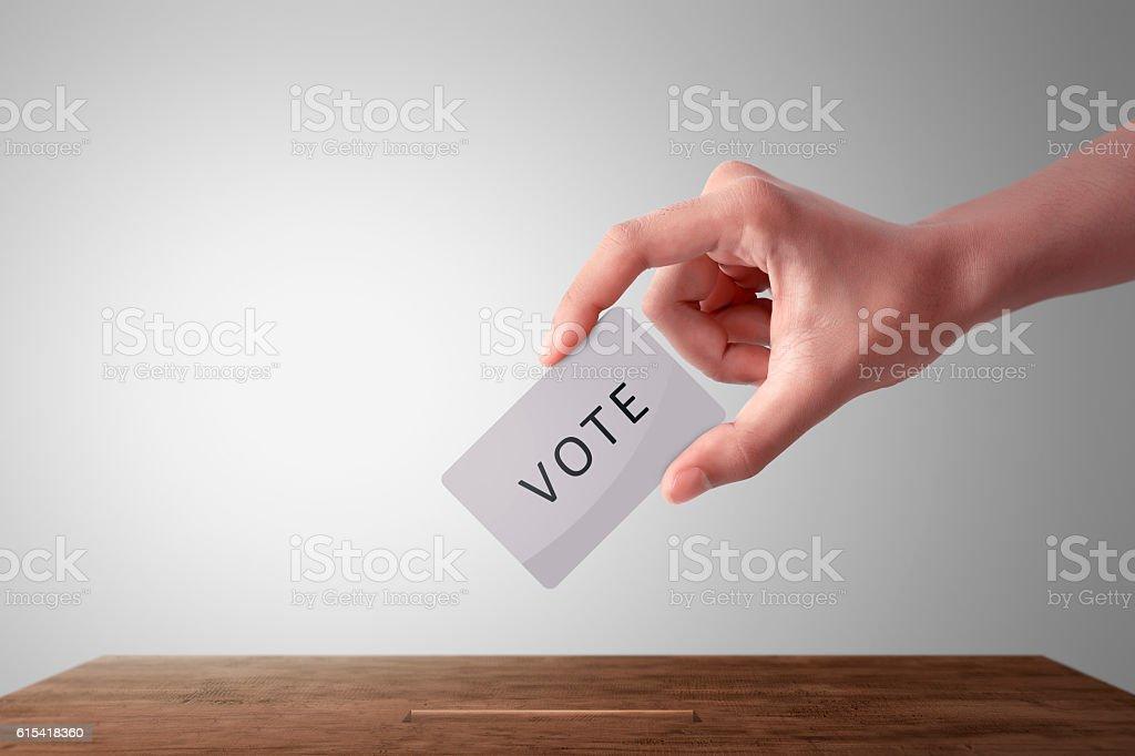 Person hand giving his vote in a ballot box stock photo