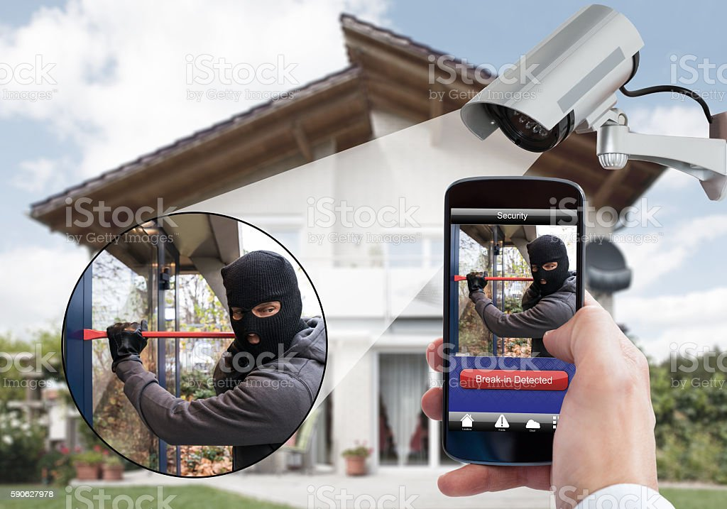 Person Hand Holding Mobile Phone Detecting Burglar stock photo