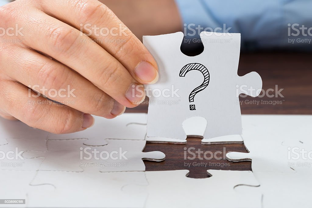 Person Hand Holding Puzzle With Question Mark stock photo