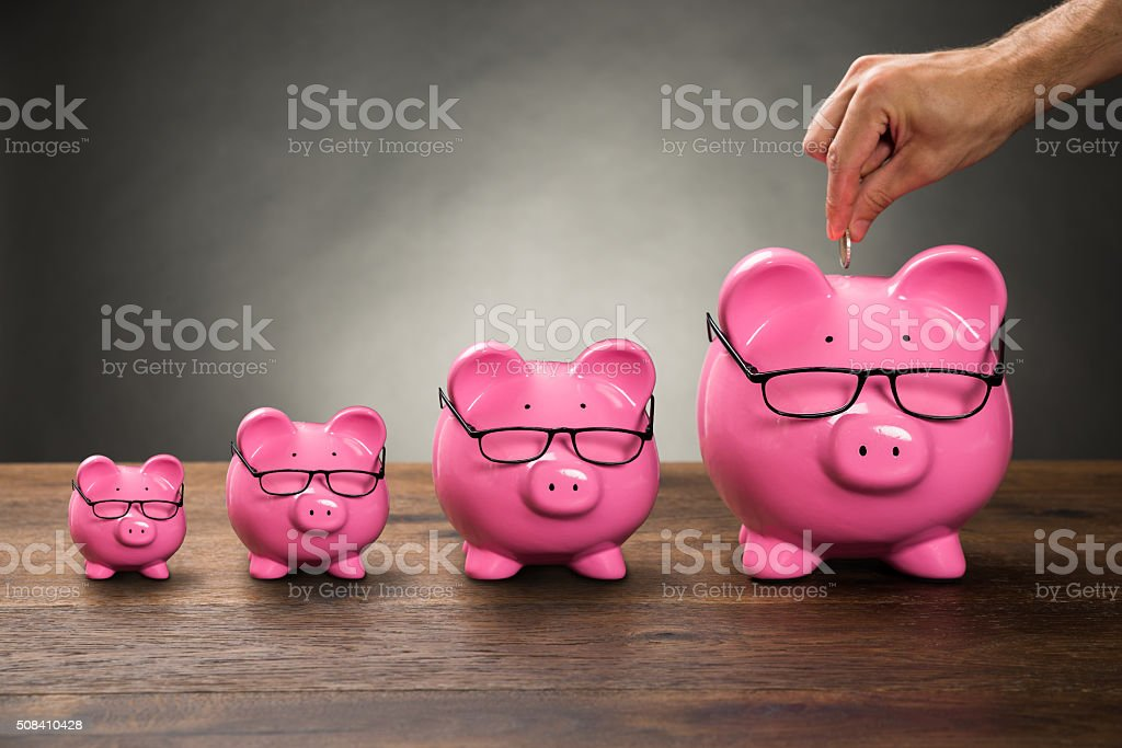 Person Hand Inserting Coin In Piggybank stock photo