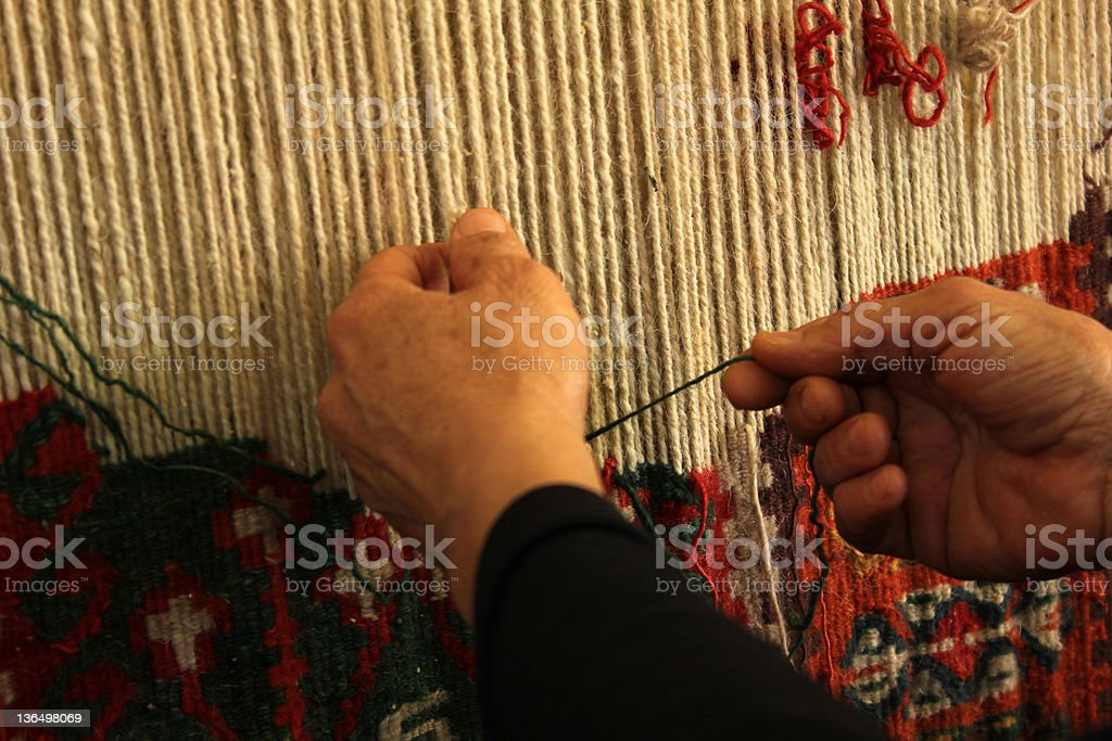 Person hand weaving rug on loom  stock photo