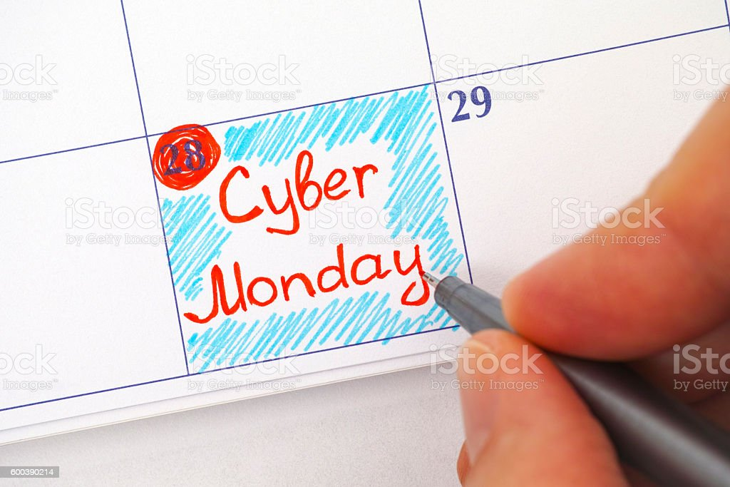 Person hand with pen writing Cyber Monday in calendar stock photo