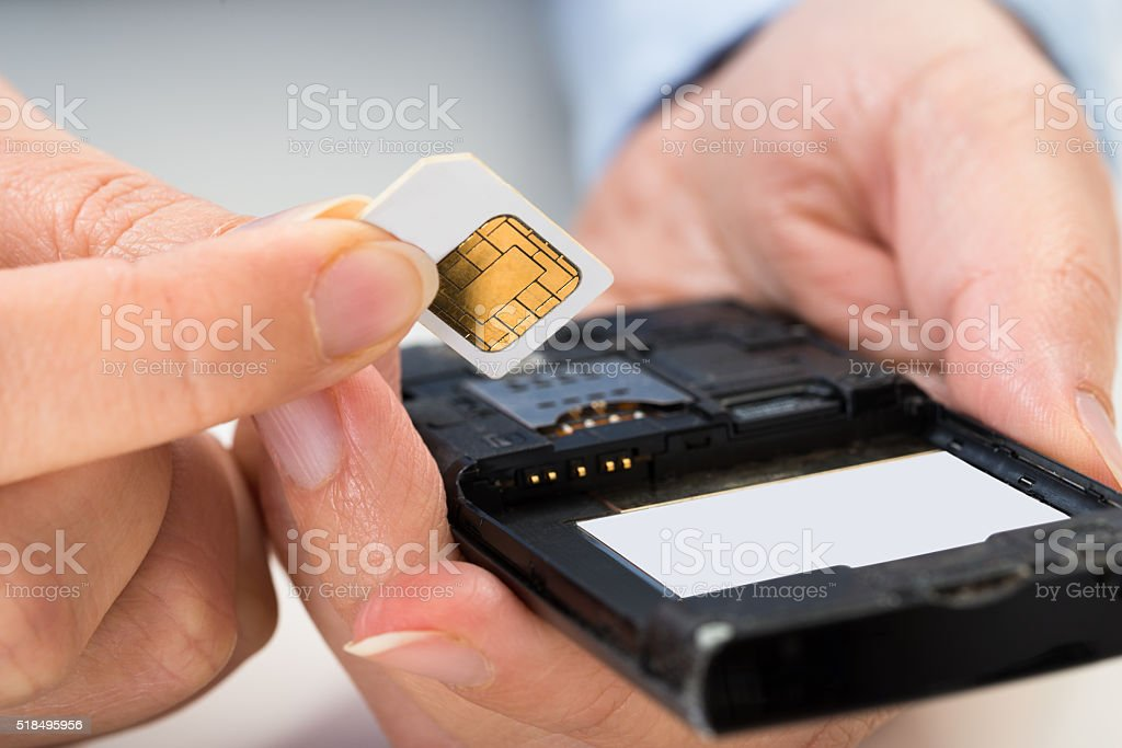 Person Hand With Sim Card And Mobile Phone stock photo