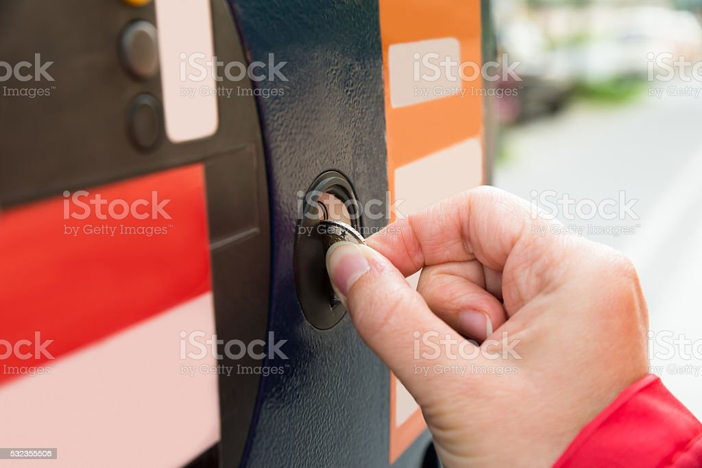 Person Hands Inserting Coin Into Parking Meter stock photo