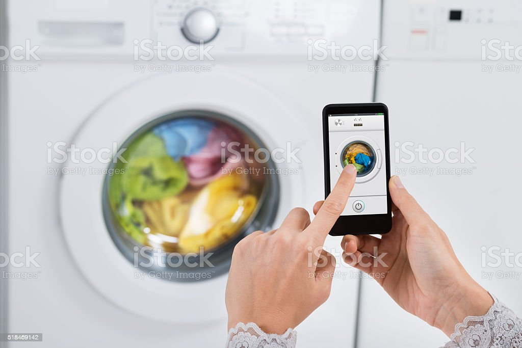 Person Hands Operating Washing Machine With Mobile Phone stock photo