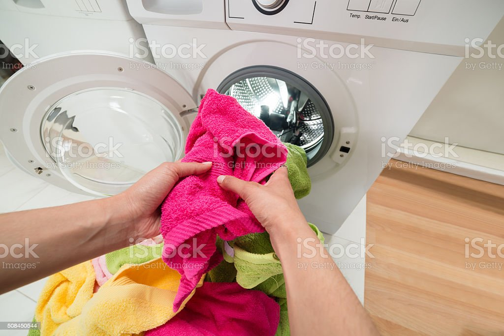 Person Hands Putting Towels Into The Washing Machine stock photo