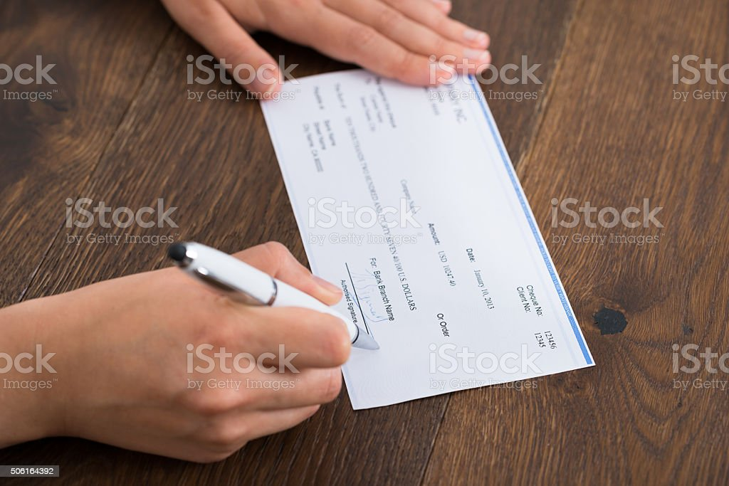 Person Hands Signing Cheque stock photo