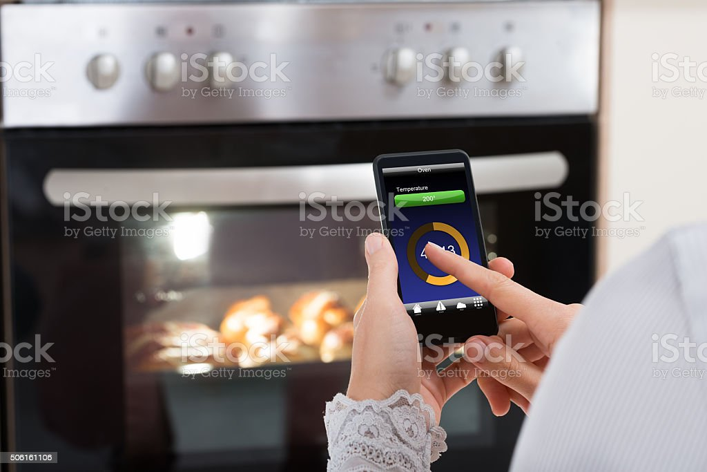 Person Hands With Mobile Phone In Front Of Oven stock photo