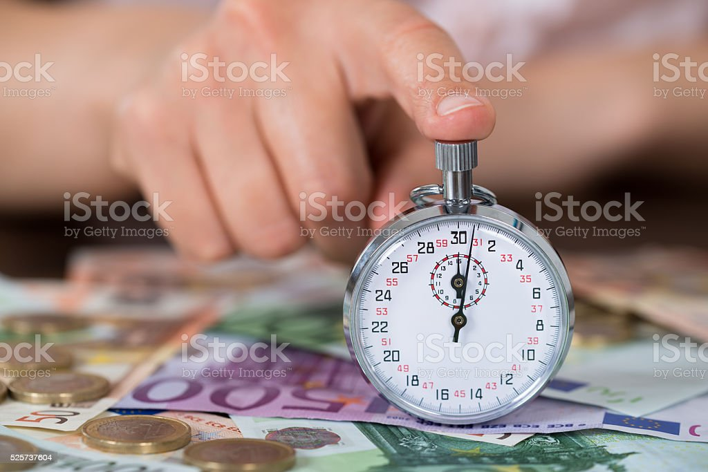 Person Hands With Stopwatch And Coins Over Banknote stock photo