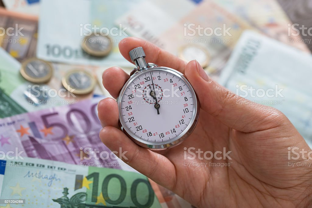Person Hands With Stopwatch Over Money stock photo