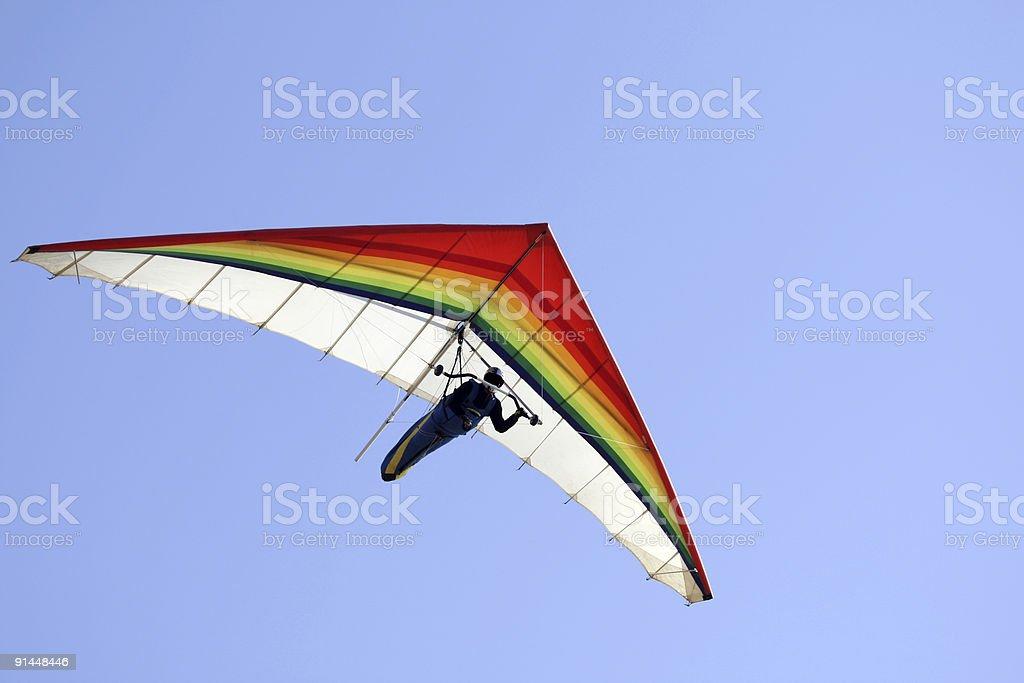 A person hang gliding on a clear day stock photo