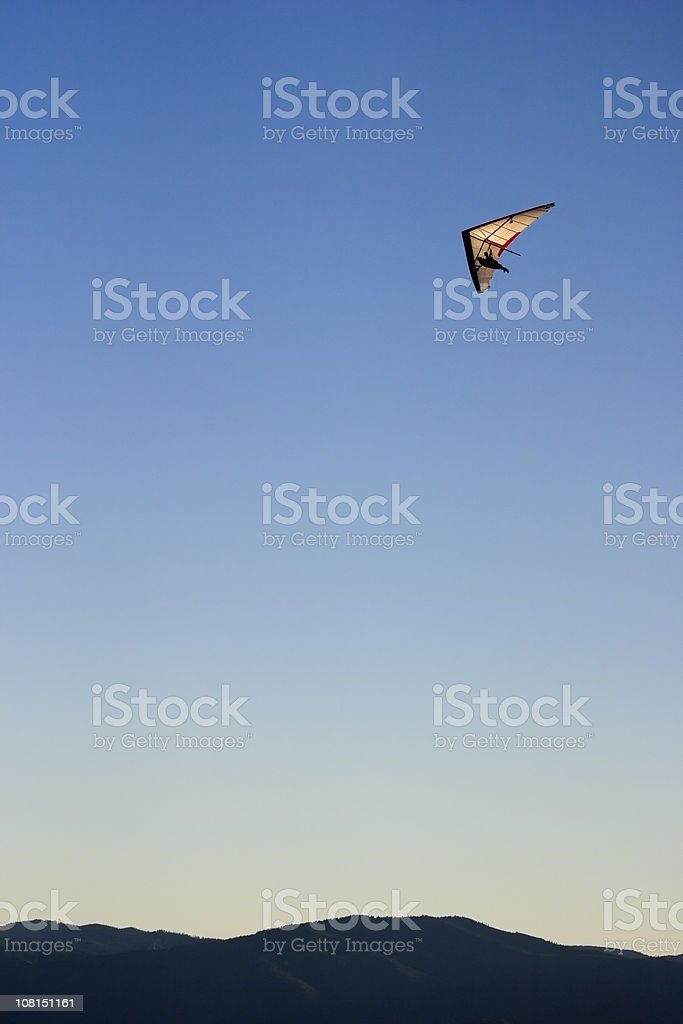 Person Hang-gliding Over Mountains Against Blue Sky royalty-free stock photo