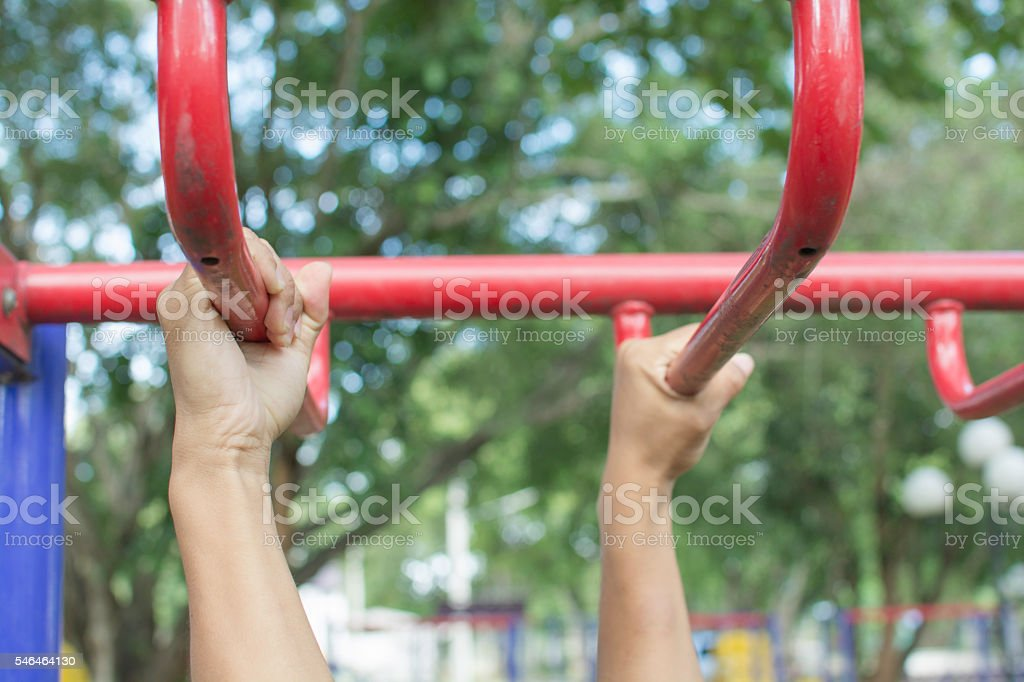 Person hanging bar the outdoor exercise equipment in public park royalty-free stock photo