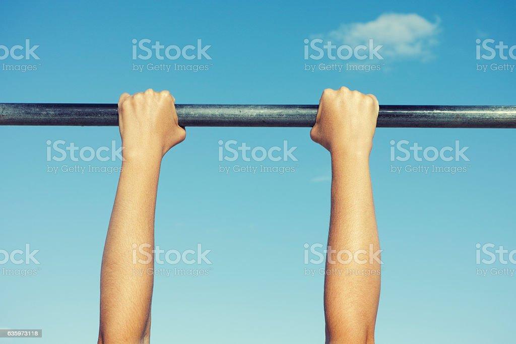 Person hanging on horizontal bar stock photo