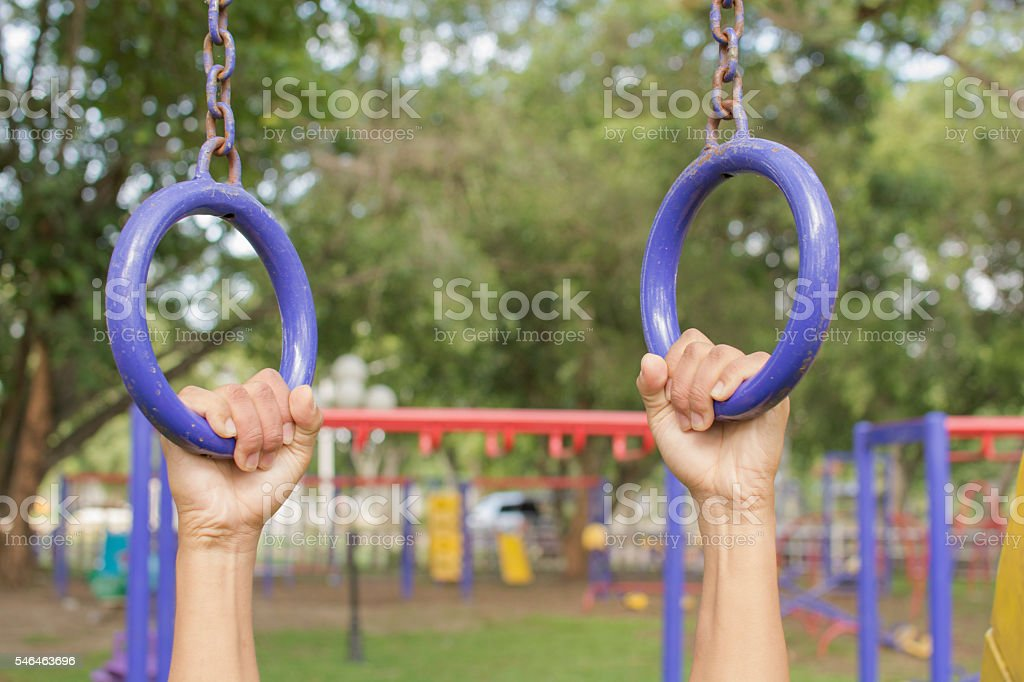 Person hanging the outdoor exercise equipment in public park royalty-free stock photo