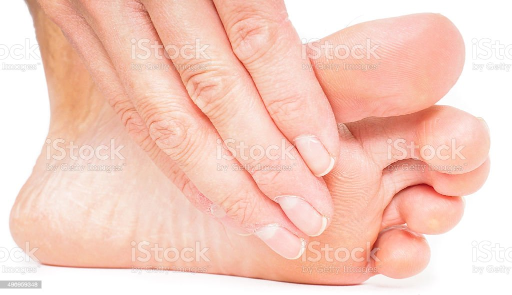 Person having pedicure, pulling hand from under foot stock photo
