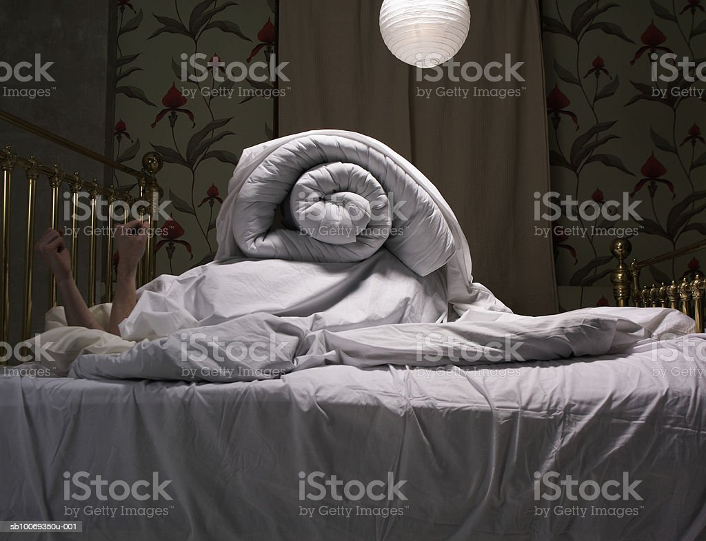 Person hiding under covers on bed stock photo