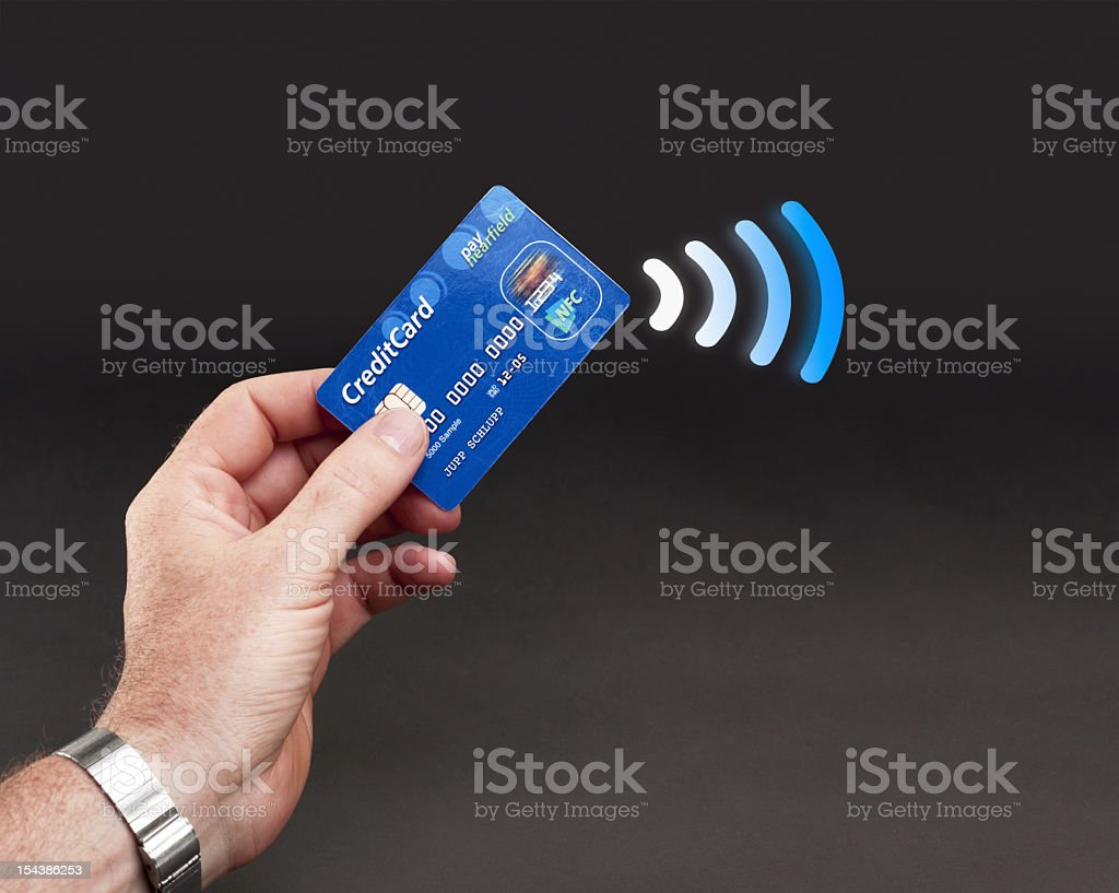 A person holding a credit card and paying electronically stock photo