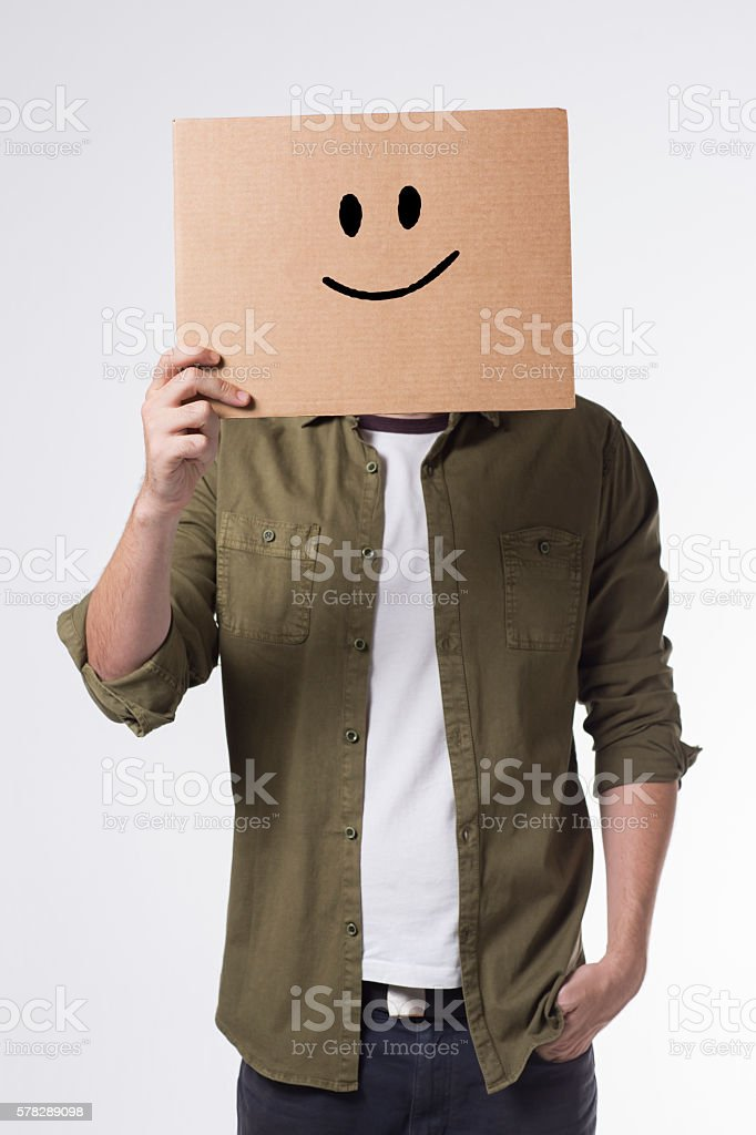 Person holding a picture of smiley face stock photo