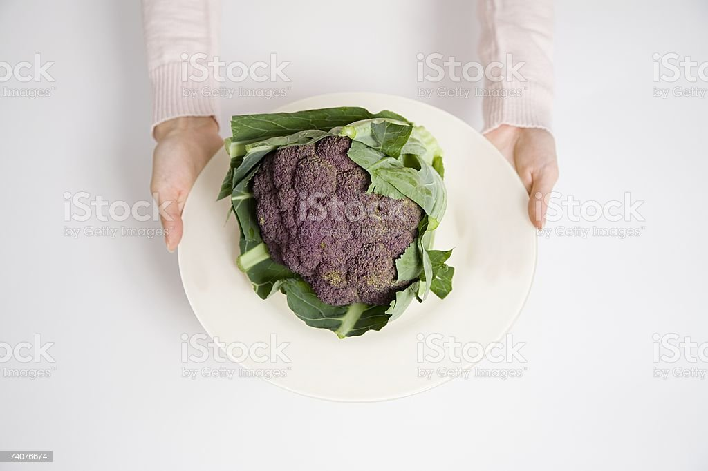 Person holding a plate of purple cauliflower stock photo