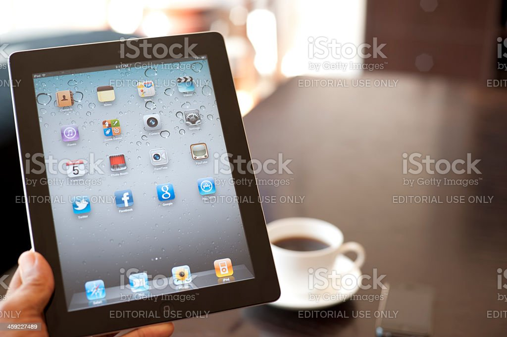 Person holding an ipad showing the home screen royalty-free stock photo