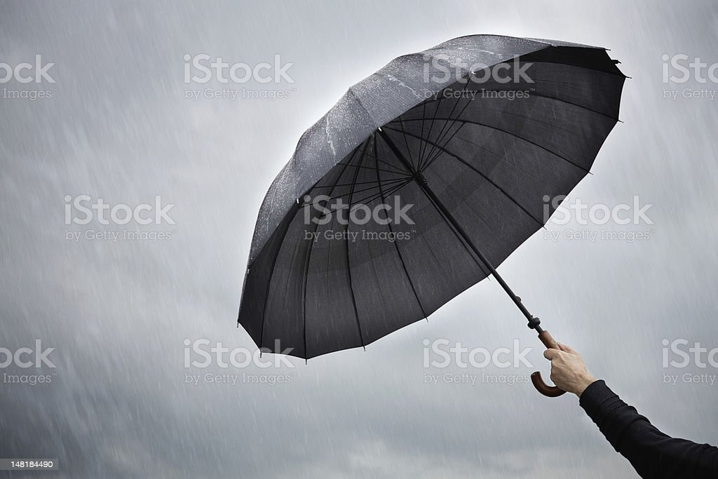 Person holding an open umbrella in the rain stock photo