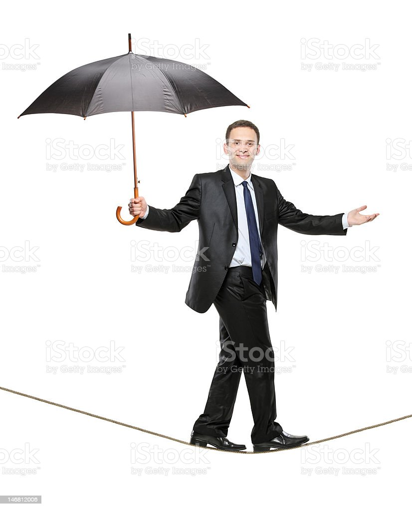 Person holding an umbrella and walking on a high tightrope royalty-free stock photo