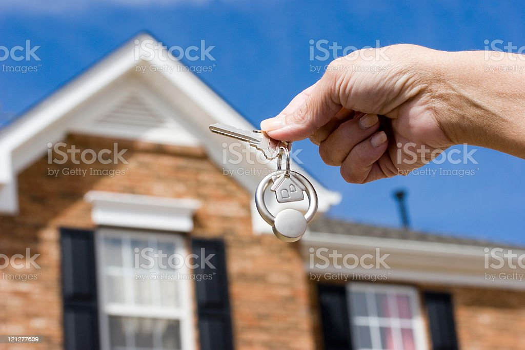 Person holding keys in front of a new house royalty-free stock photo