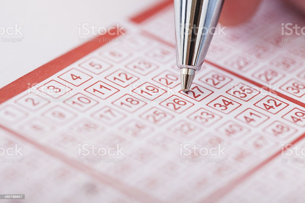 Person Holding Pen Over Lottery Ticket stock photo