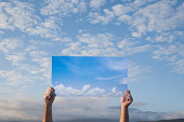 Person holding photo of sky against sky outdoors