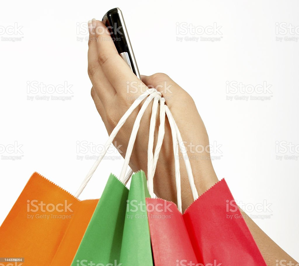 A person holding shopping bags and texting royalty-free stock photo