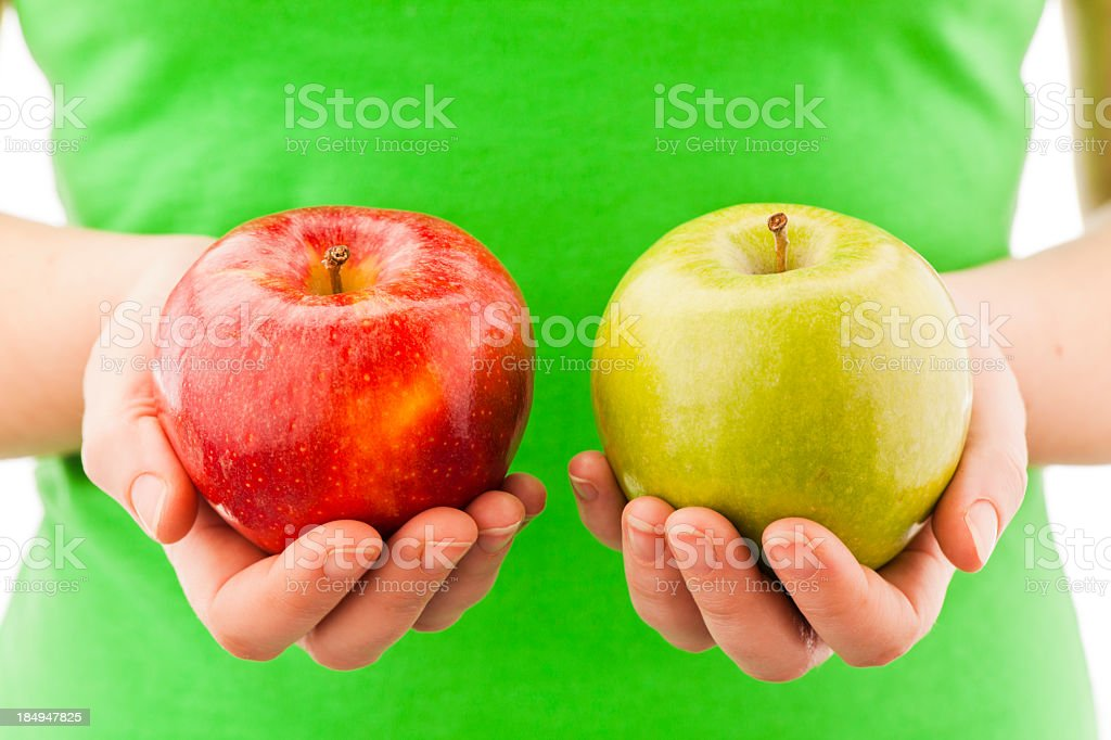 A person holding two apples in their hands stock photo
