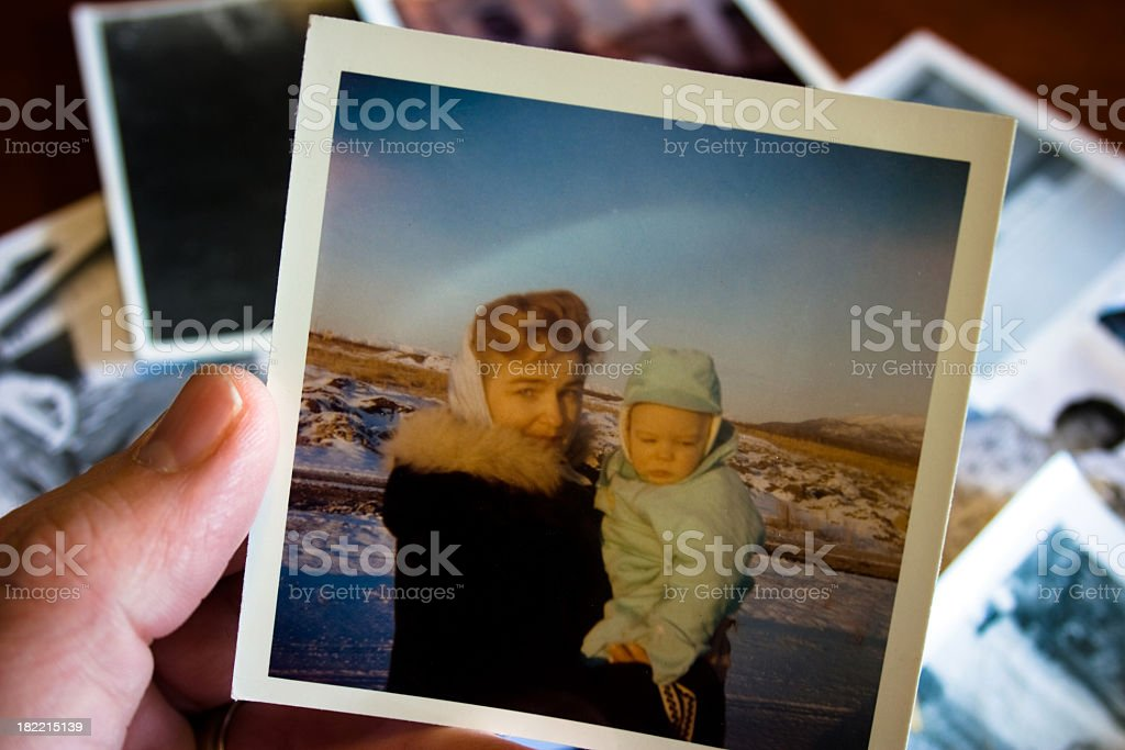 Person holding vintage photo of mother and child stock photo