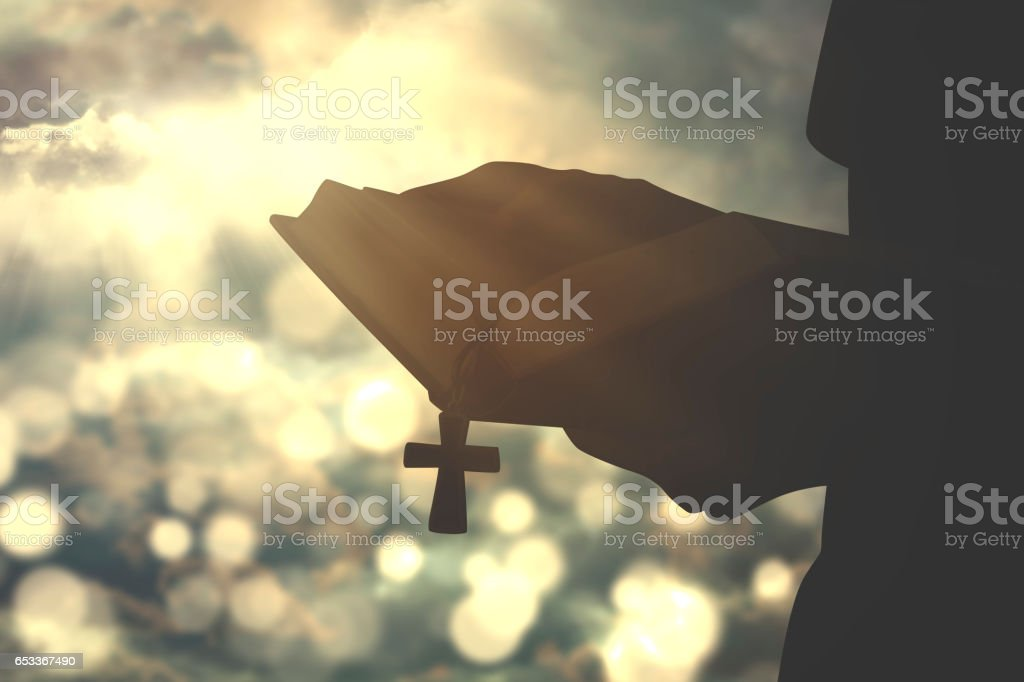 Person holds bible with crucifix symbol stock photo