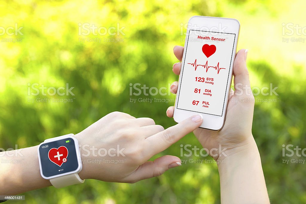 Person holds smartphone and wears health sensor stock photo