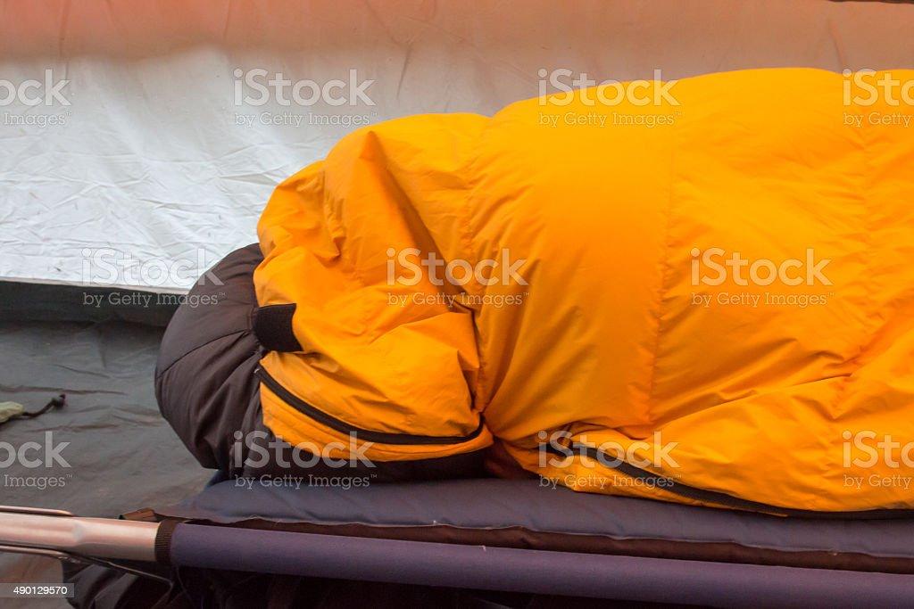 Person in an orange mummy sleeping bag stock photo