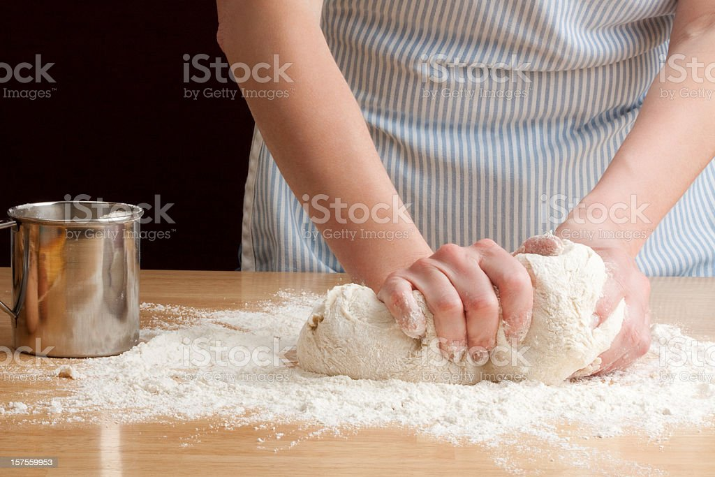 Person in apron kneading dough to make bread stock photo