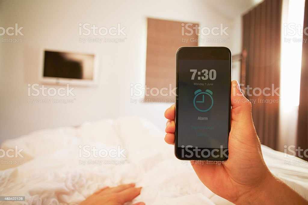 Person In Bed Turning Off Phone Alarm stock photo