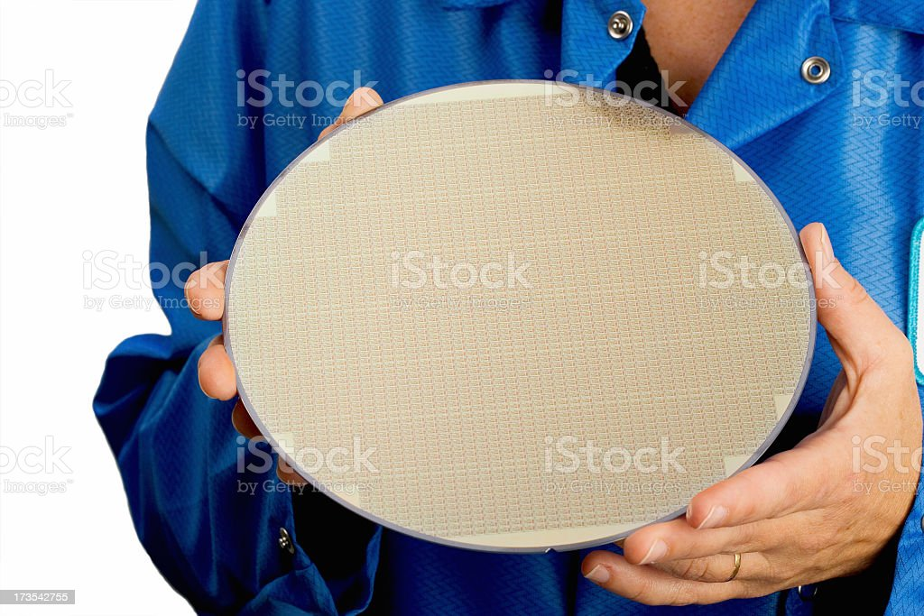 Person in blue holding a large silicone wafer stock photo