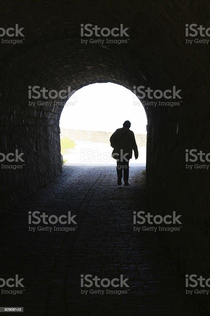 person in dark tunnel stock photo