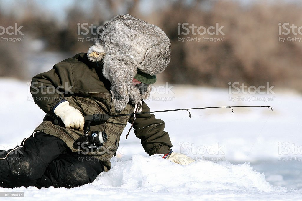 Person in full winter gear ice fishing from a frozen lake stock photo