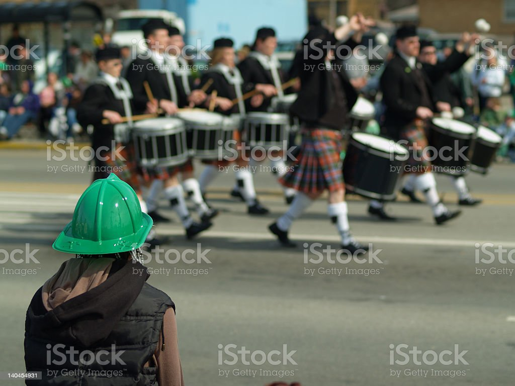 Person in green hat watching drummers walk by in the parade royalty-free stock photo