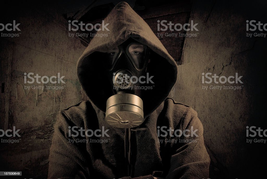 Person in hood wearing gas mask stock photo