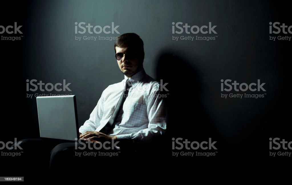 A person in sunglasses and a tie on a laptop in a dark room stock photo