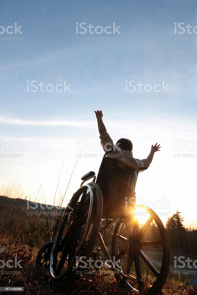 Person in wheelchair with arms up, praising the sunset royalty-free stock photo