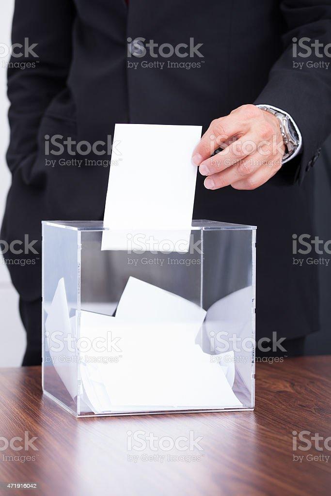 Person Inserting Ballot In Box stock photo
