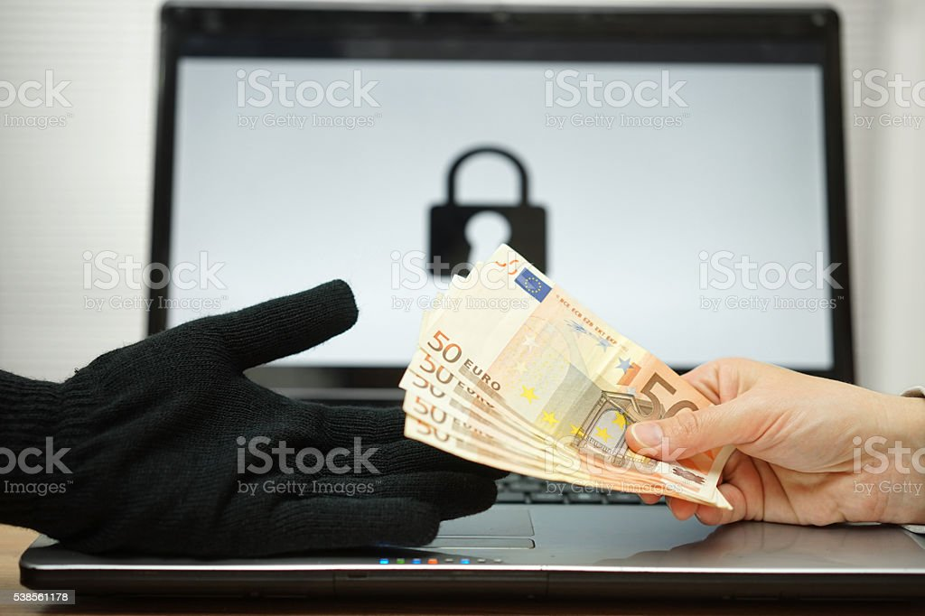 person is giving money to computer hacker to decrypt files, stock photo