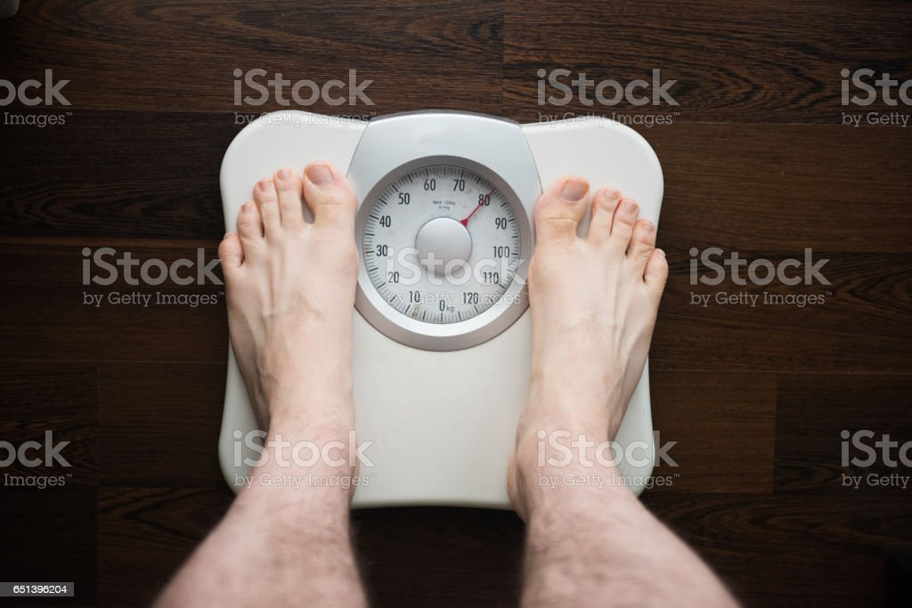 A person is standing on a weight scale or scales to check the body weight stock photo