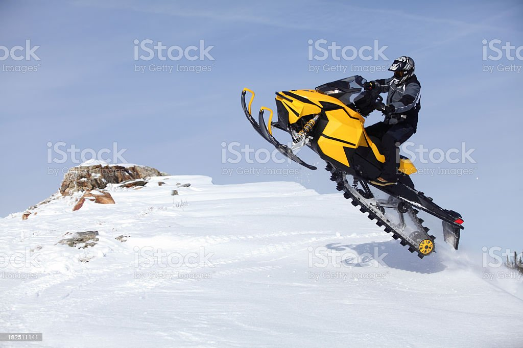 Person jumping a yellow snowmobile stock photo