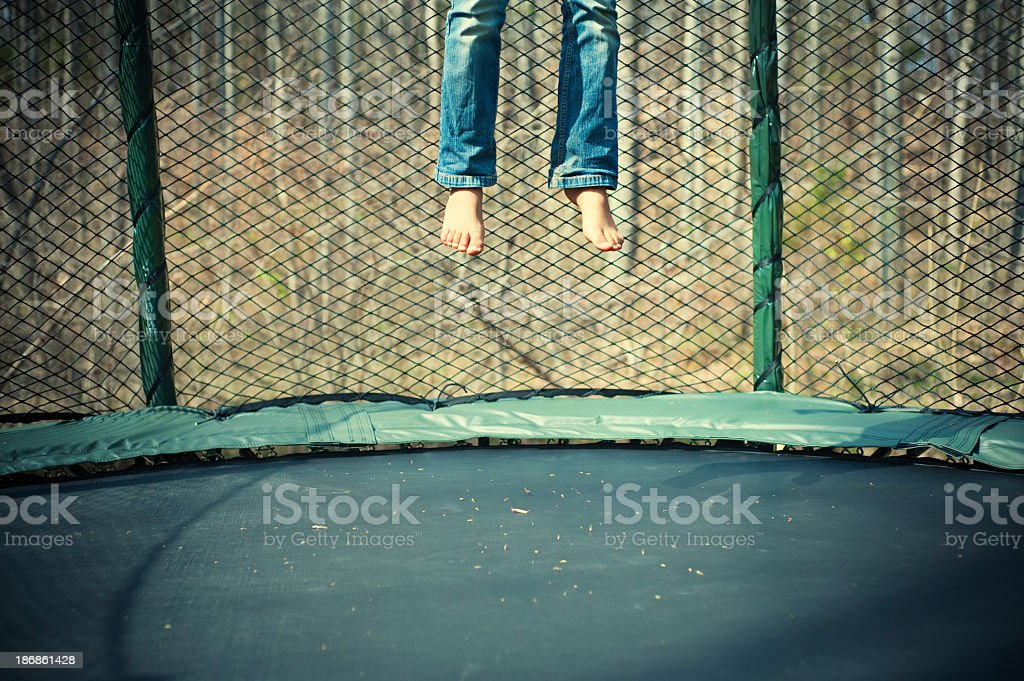 Person jumping in a trampoline stock photo